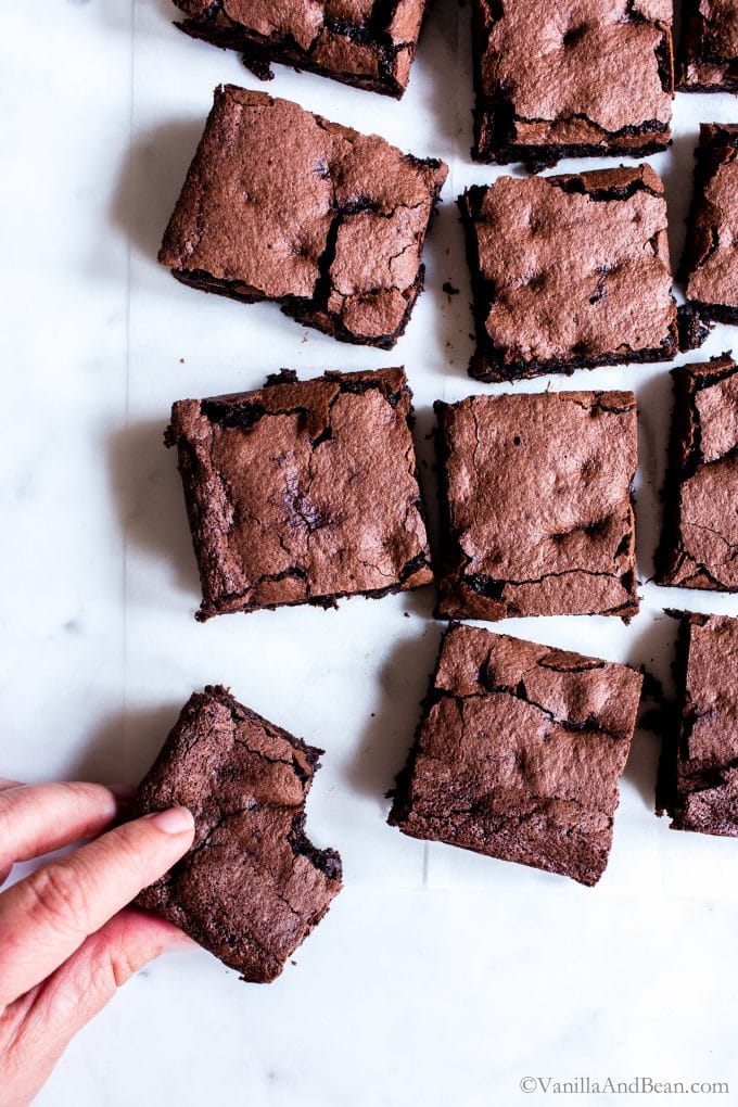 Multiple espresso brownies with a hand taking one.