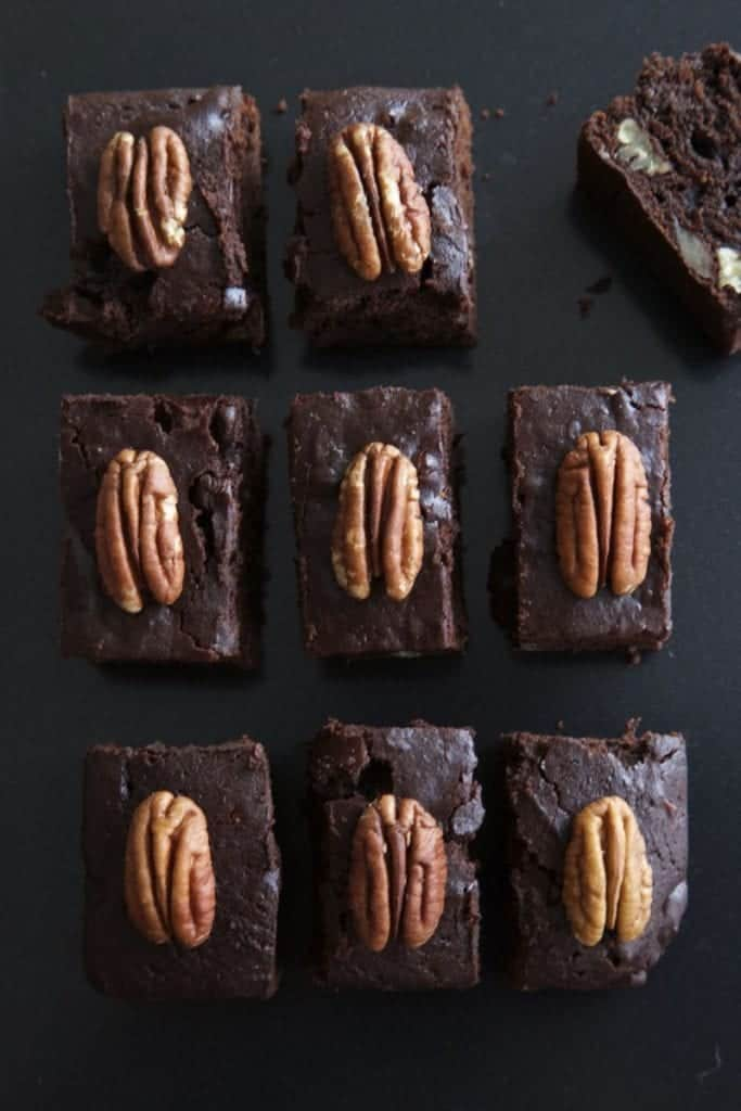 Multiple pecan and pumpkin brownies  on a black surface, with pecan on top.