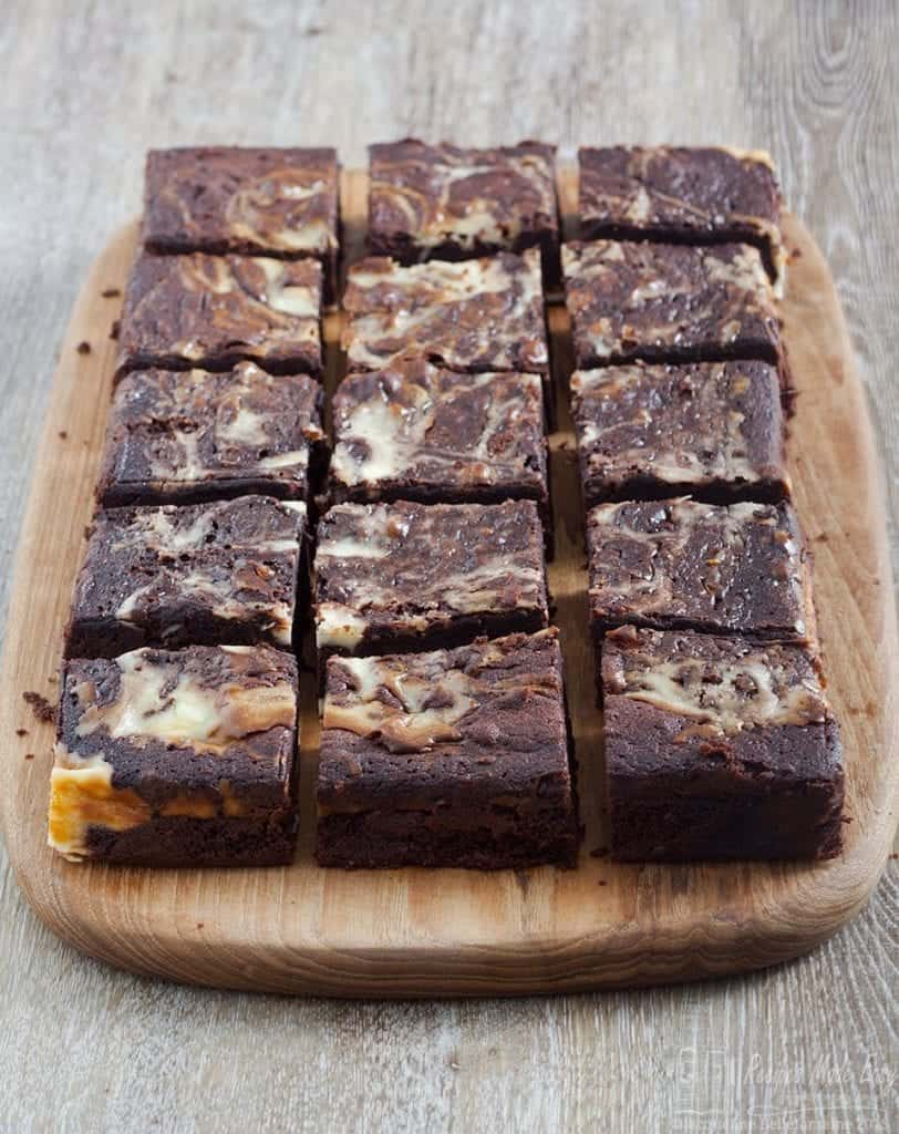Multiple cheesecake brownies on a wooden board.