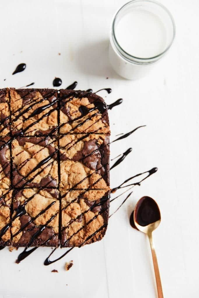 Peanut butter cookie brownies with chocolate sauce and a glass of milk.
